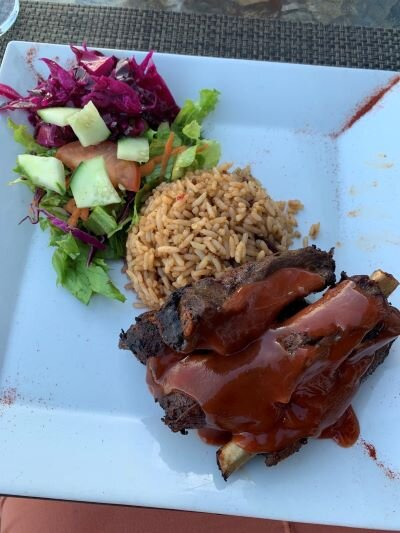 Antiguan ribs, rice, and salad on a white plate.