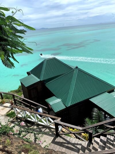 Steps lead down to a green-roofed building by the water while a person rides a jet ski across the waves at COCOS Hotel.