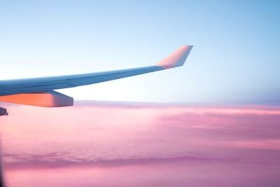 The wing of an airplane, lit from below by the setting sun, juts out over a sea of pink clouds.