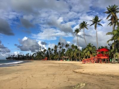 A sandy stretch of beach dotted with red cabanas in Luquillo, Puerto