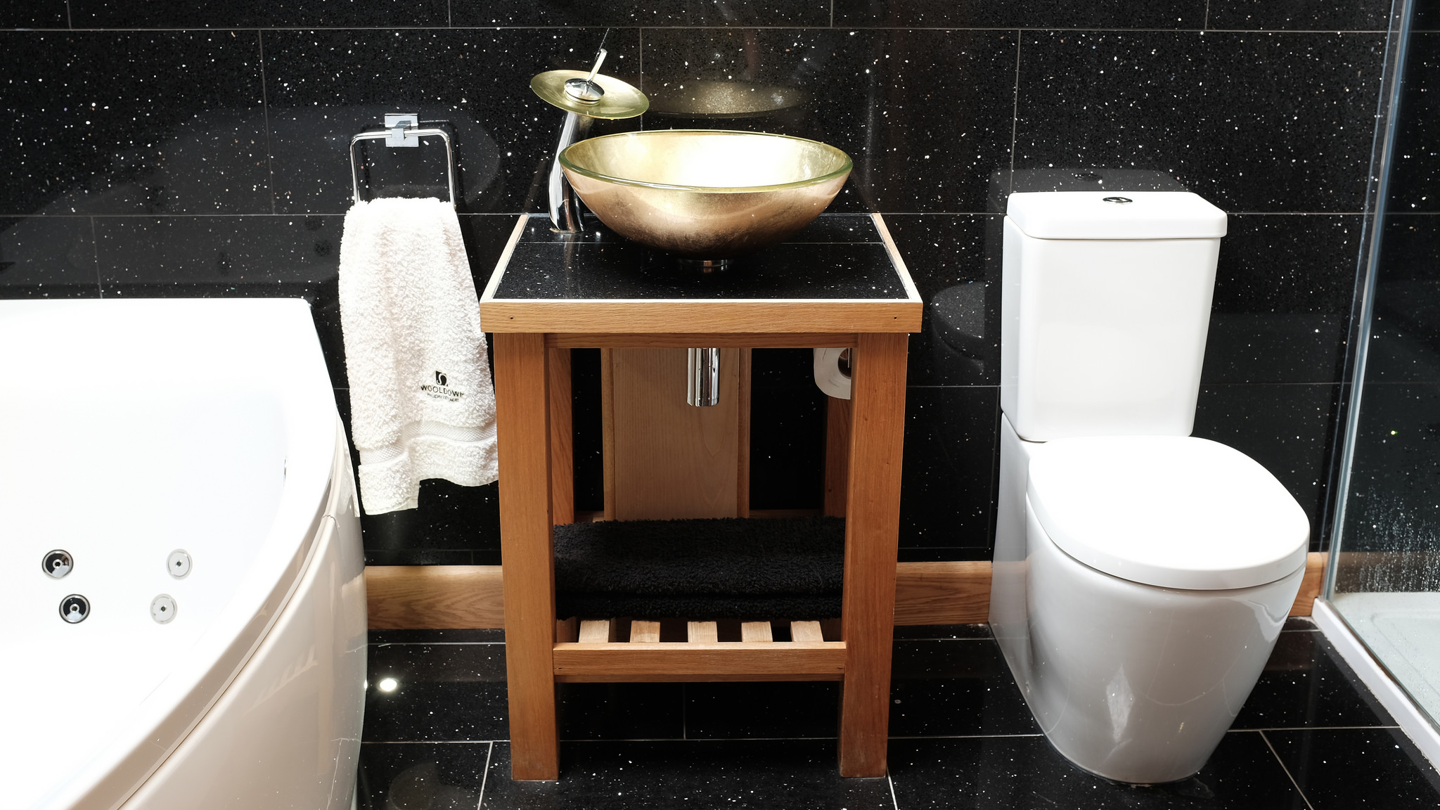 Bathroom with spa bath and gold round hand basin with waterfall tap