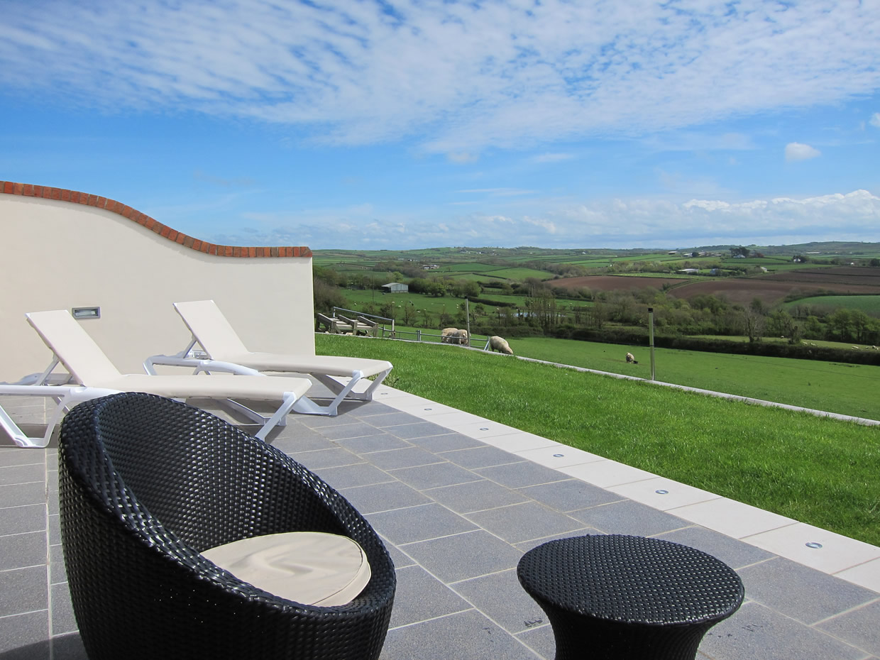 Private patio area with sun loungers and seating