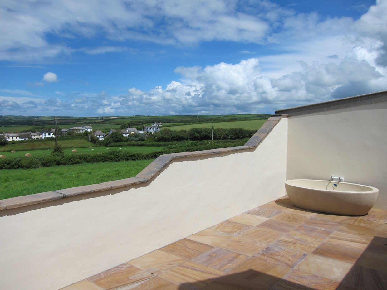 Patio area with outside bath, sea and countryside views towards Bude