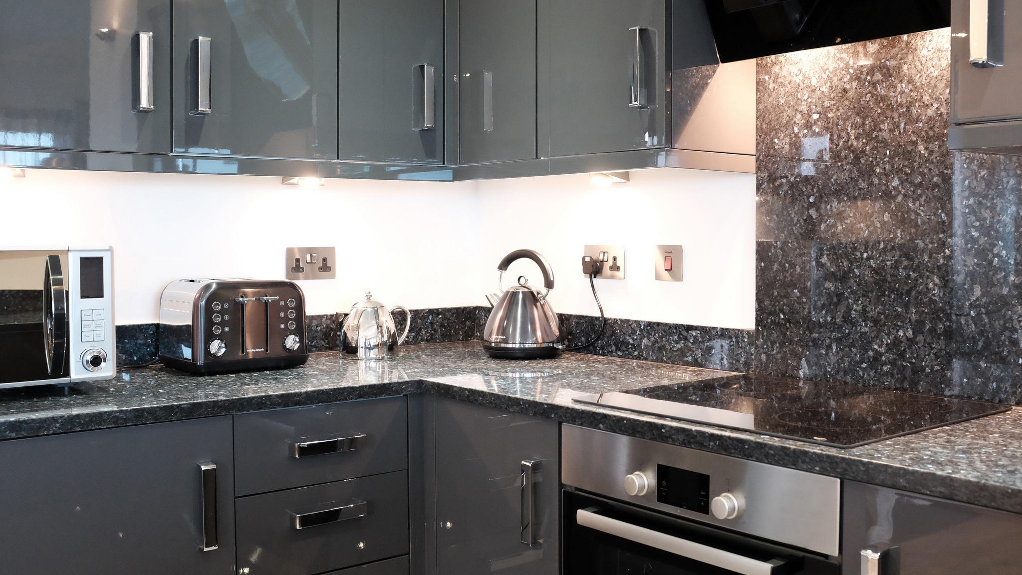 "Grey open-plan kitchen with shimmering ""Blue Pearl"" granite worktop"