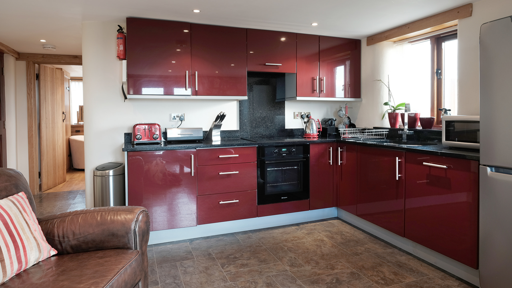 Red glossy kitchen with black granite worktop and red accessories