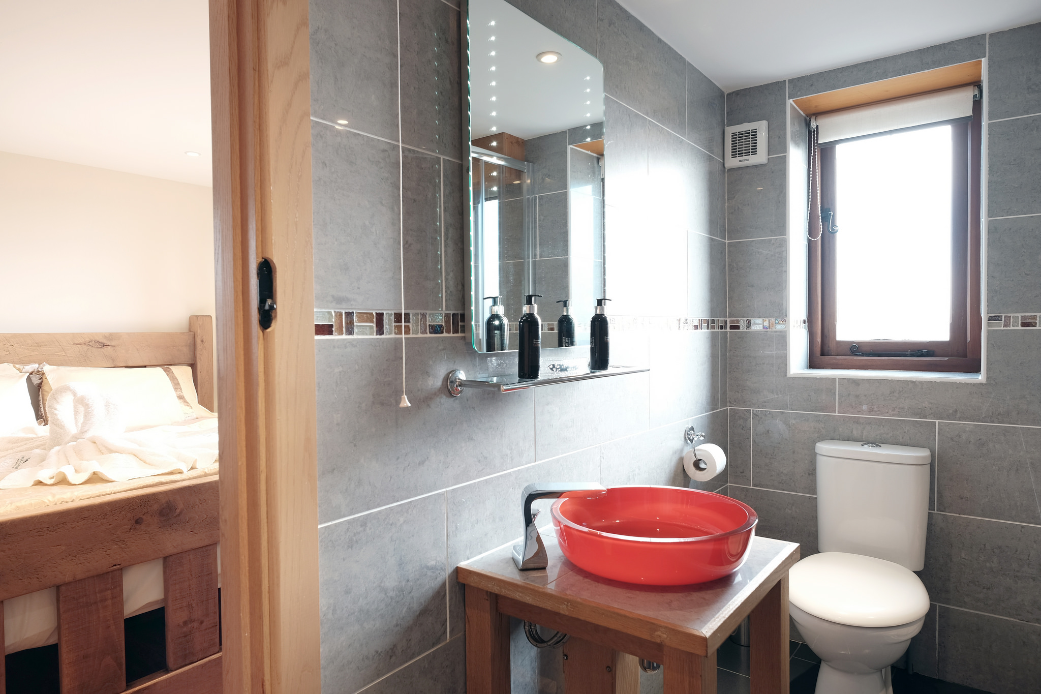 Bedroom and the bathroom with red sink and LED mirror