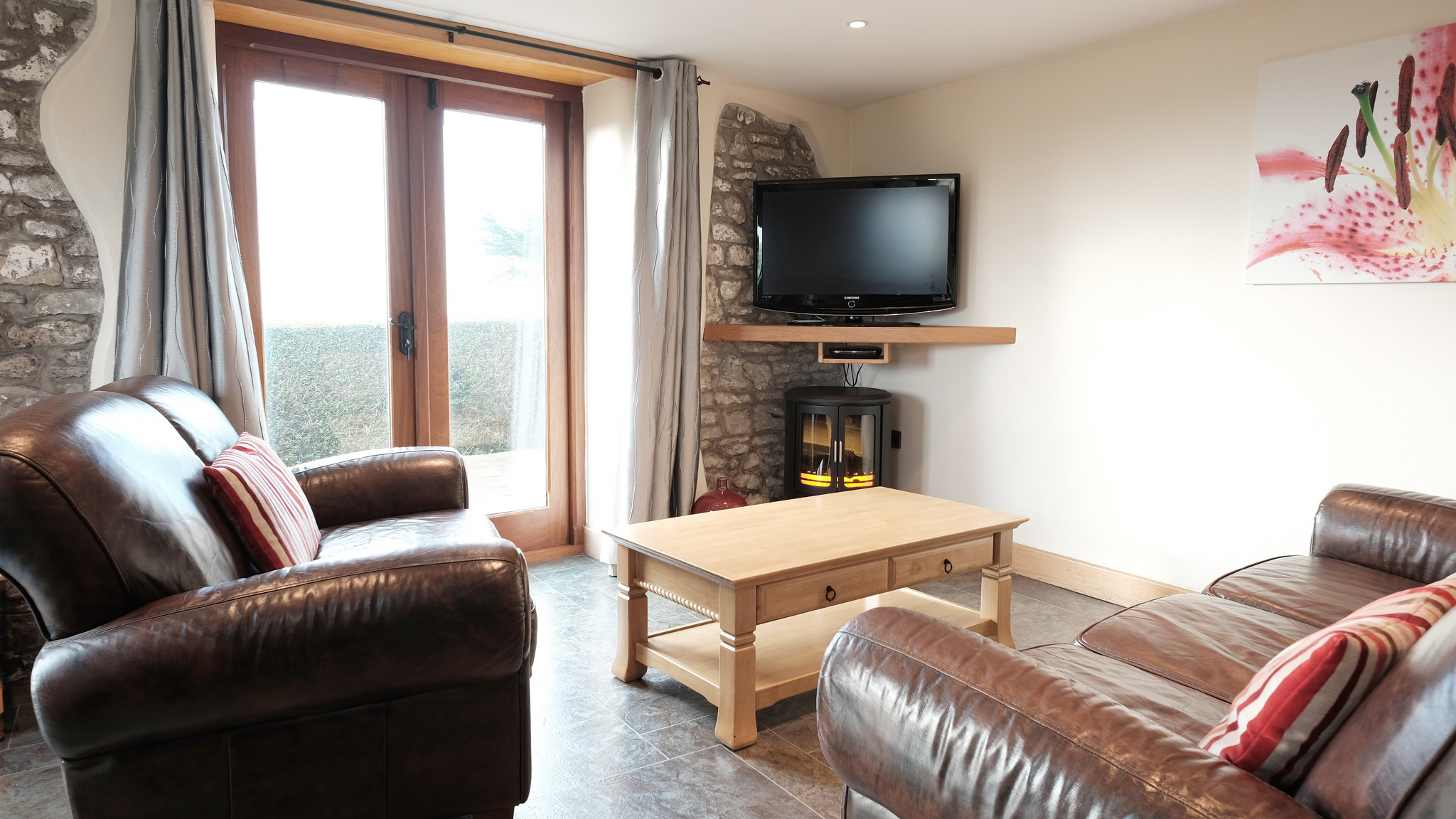 Living area with two leather sofas, TV and electric fire