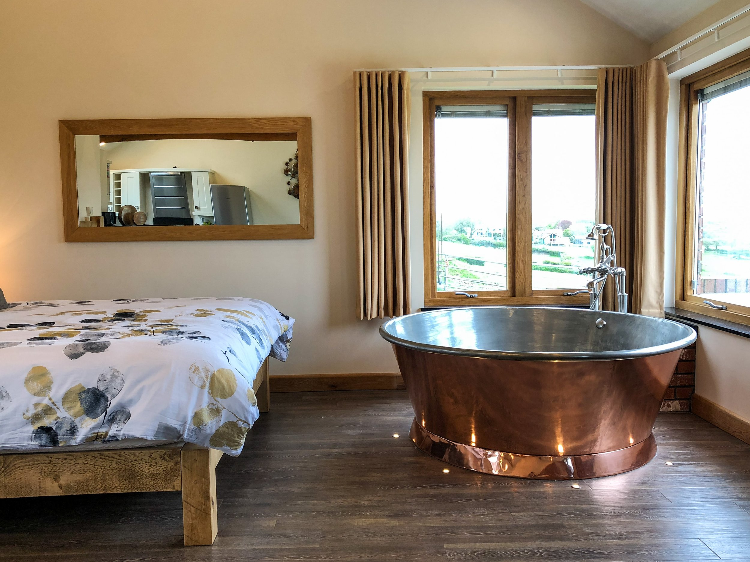 Copper spa bath with the super king-size Canadian pine plank bed