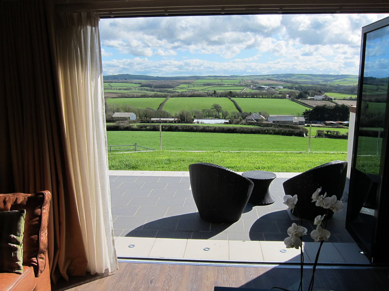 Open bi-fold doors with Cornish countryside views