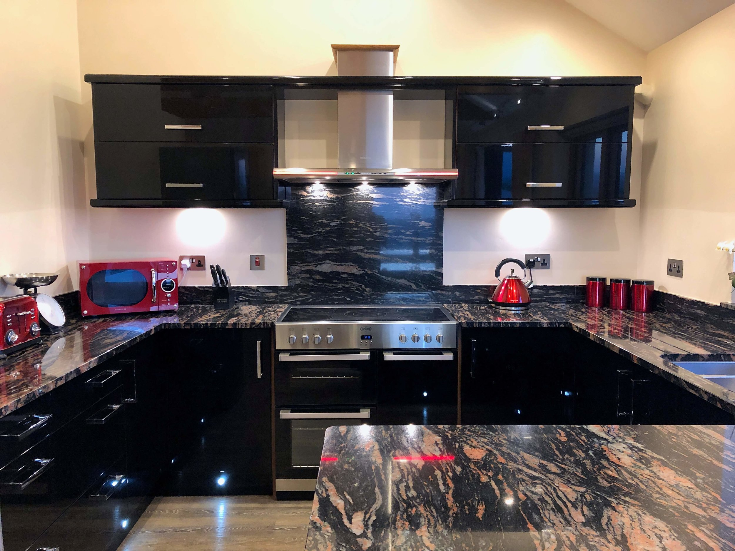 Modern black gloss kitchen with black and red flecked granite worktops