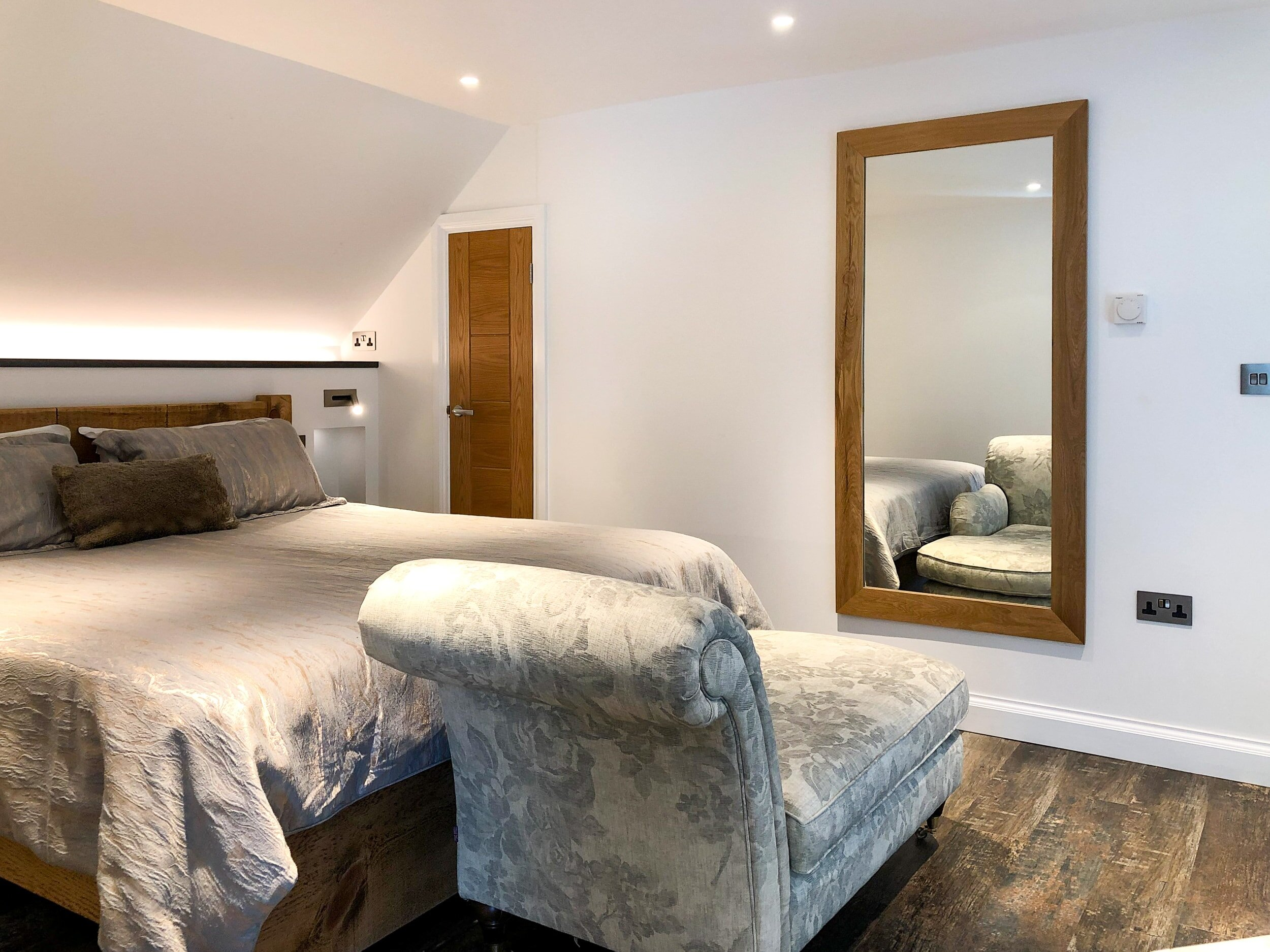 Open plan bedroom with large mirror