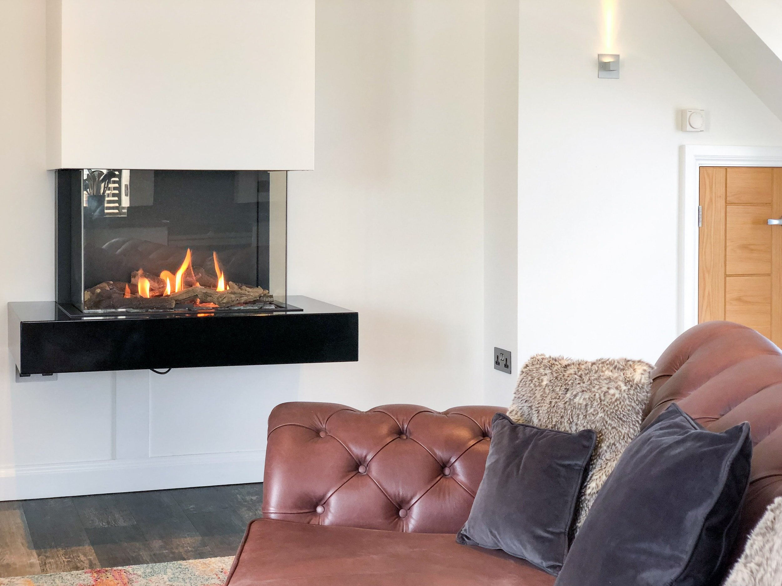 Cosy living area with leather sofa and gas fire