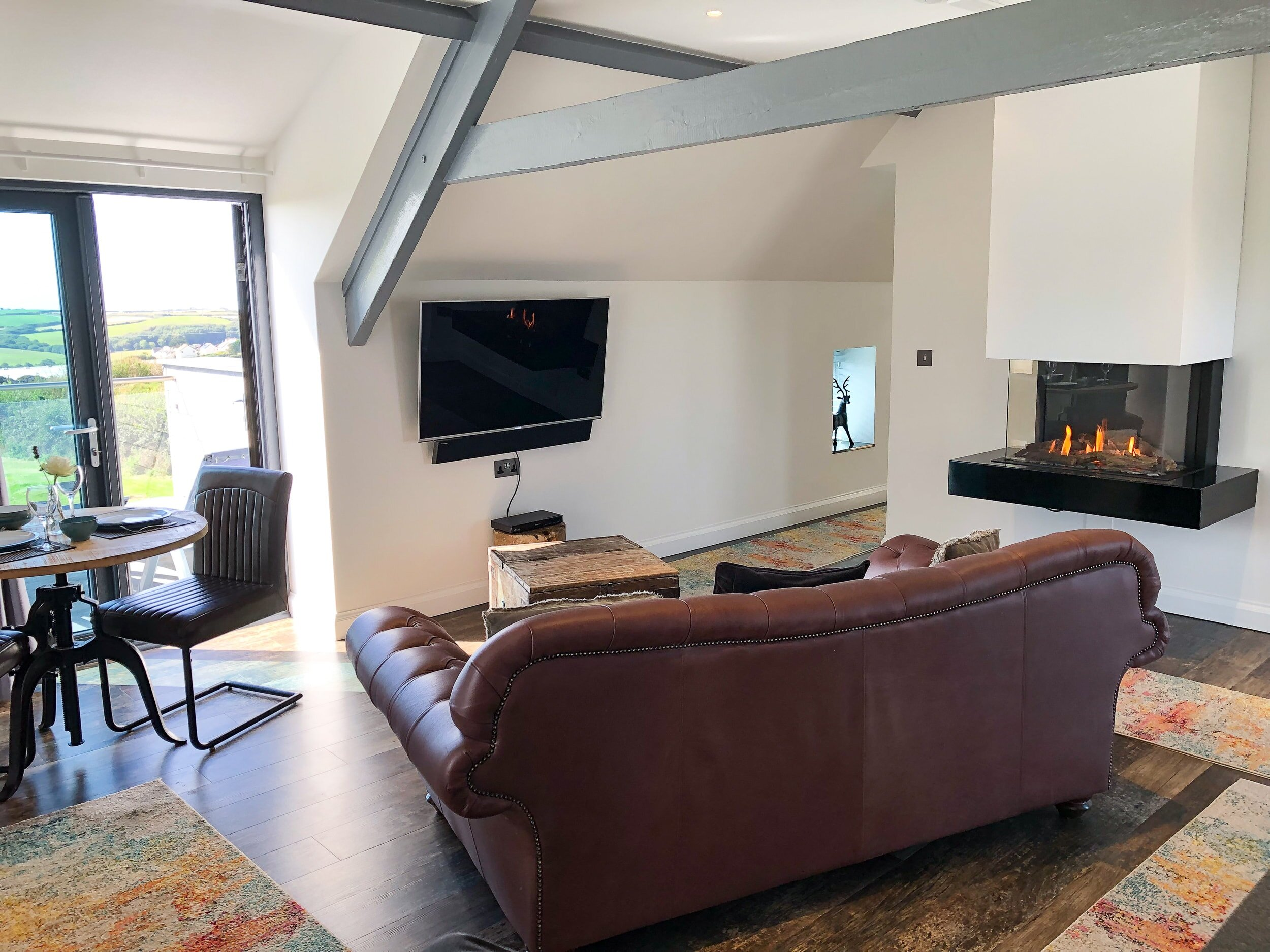 Large leather sofa for two in front of the flat screen TV and gas fire place