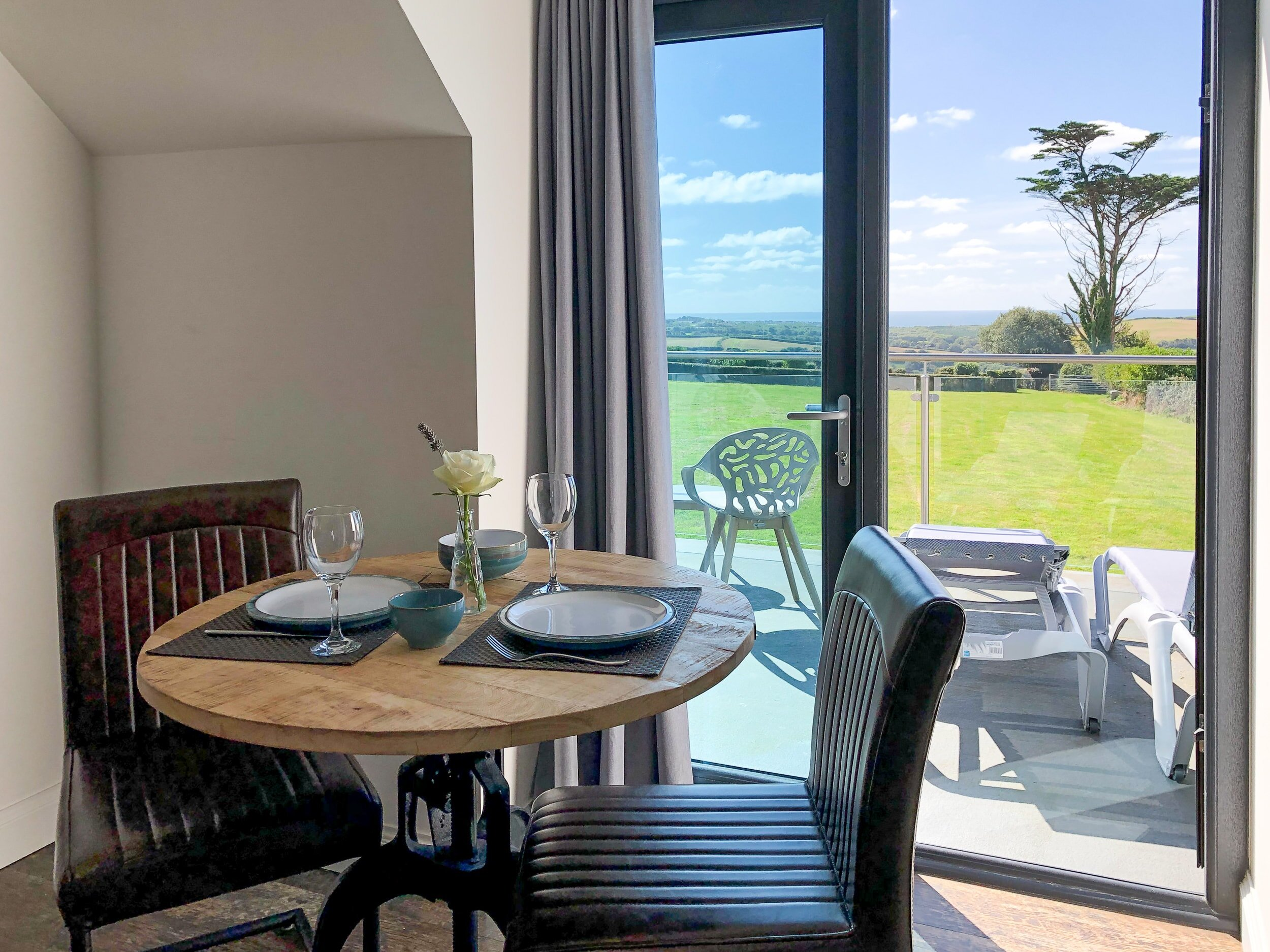Dining area for two people with countryside and sea views towards Widemouth Bay