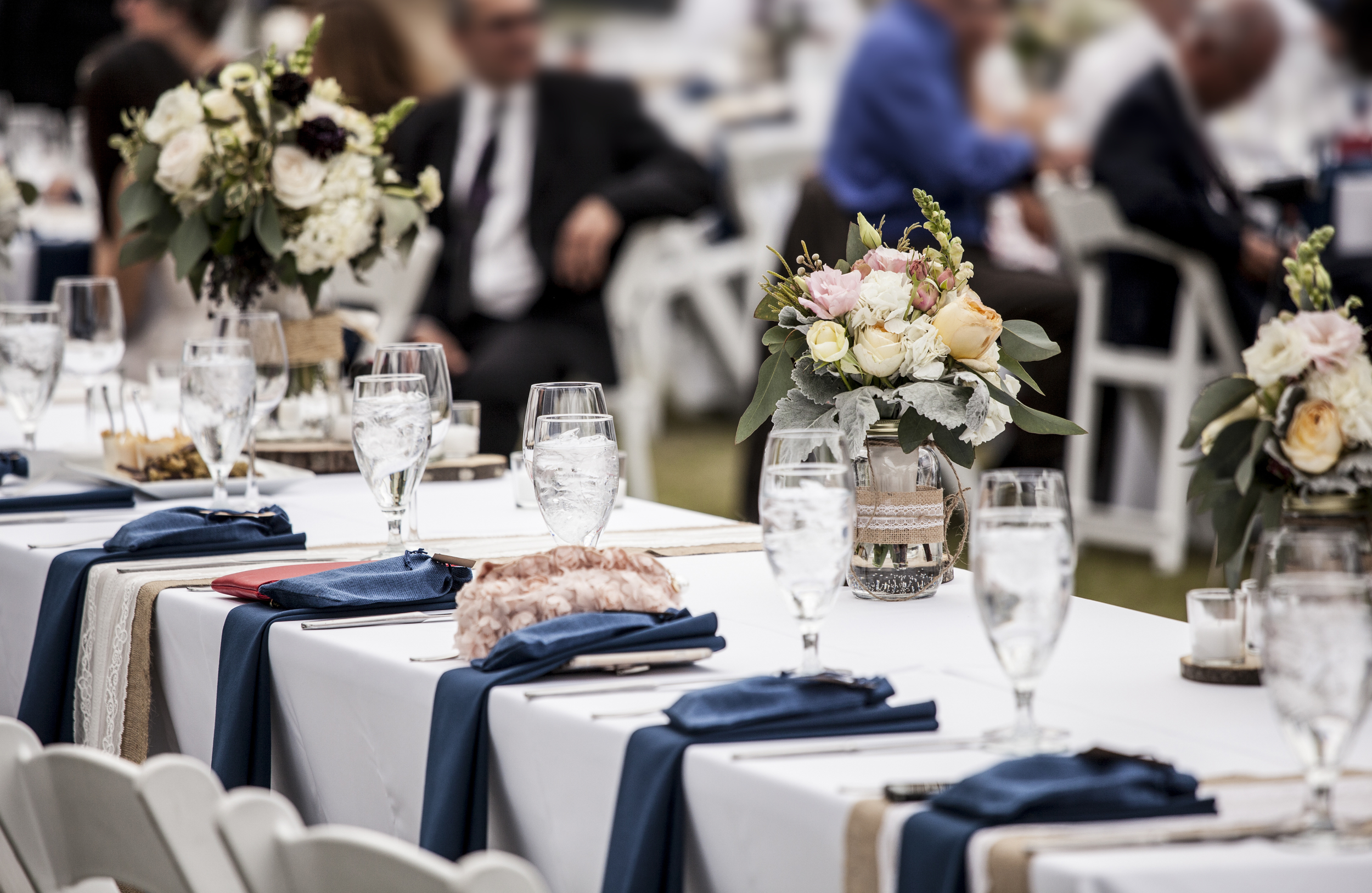 Table set up for wedding reception with people out of focus in background.png
