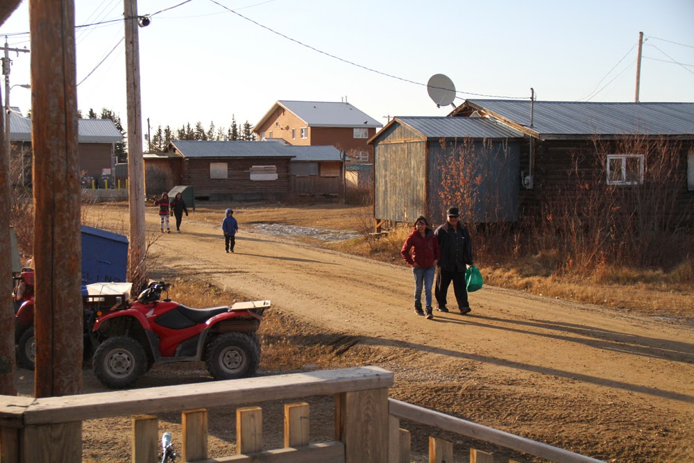 Joel and Precilla walk arm-in-arm toward the community hall