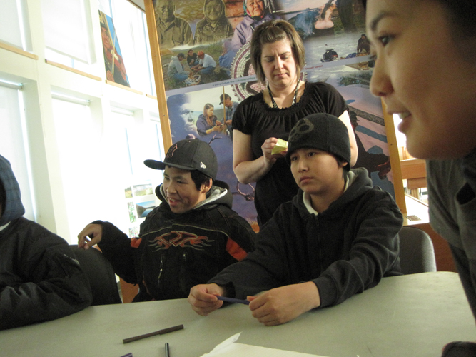 Darcy and Marlon think while teacher Keri looks on.