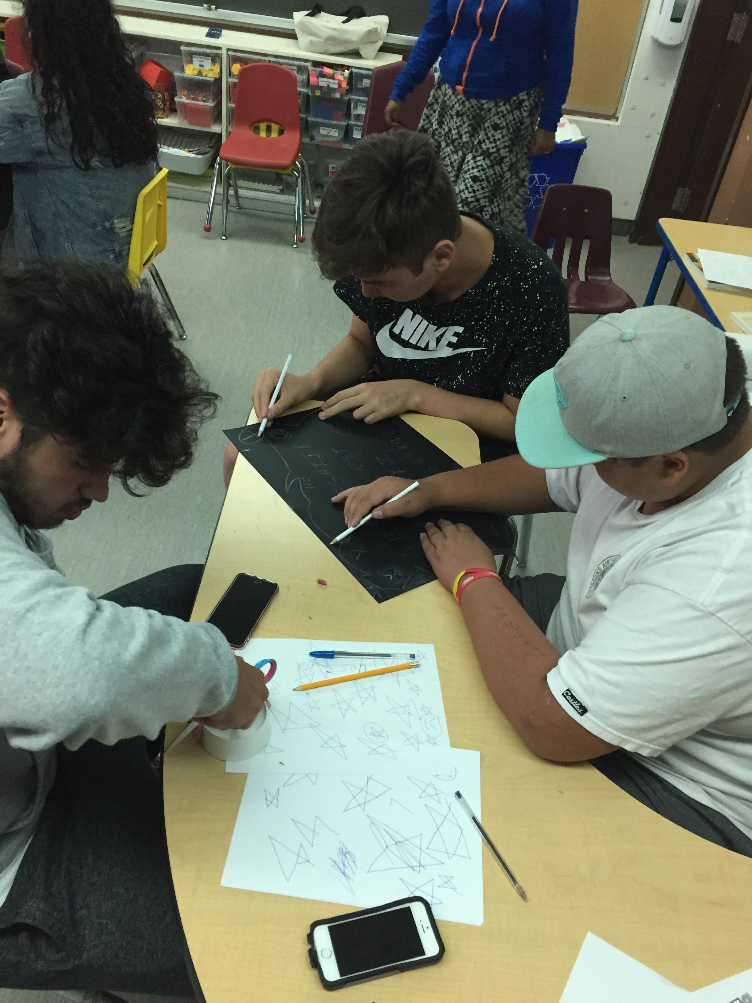 Dorian, Gabe and Cylus create their ouija board