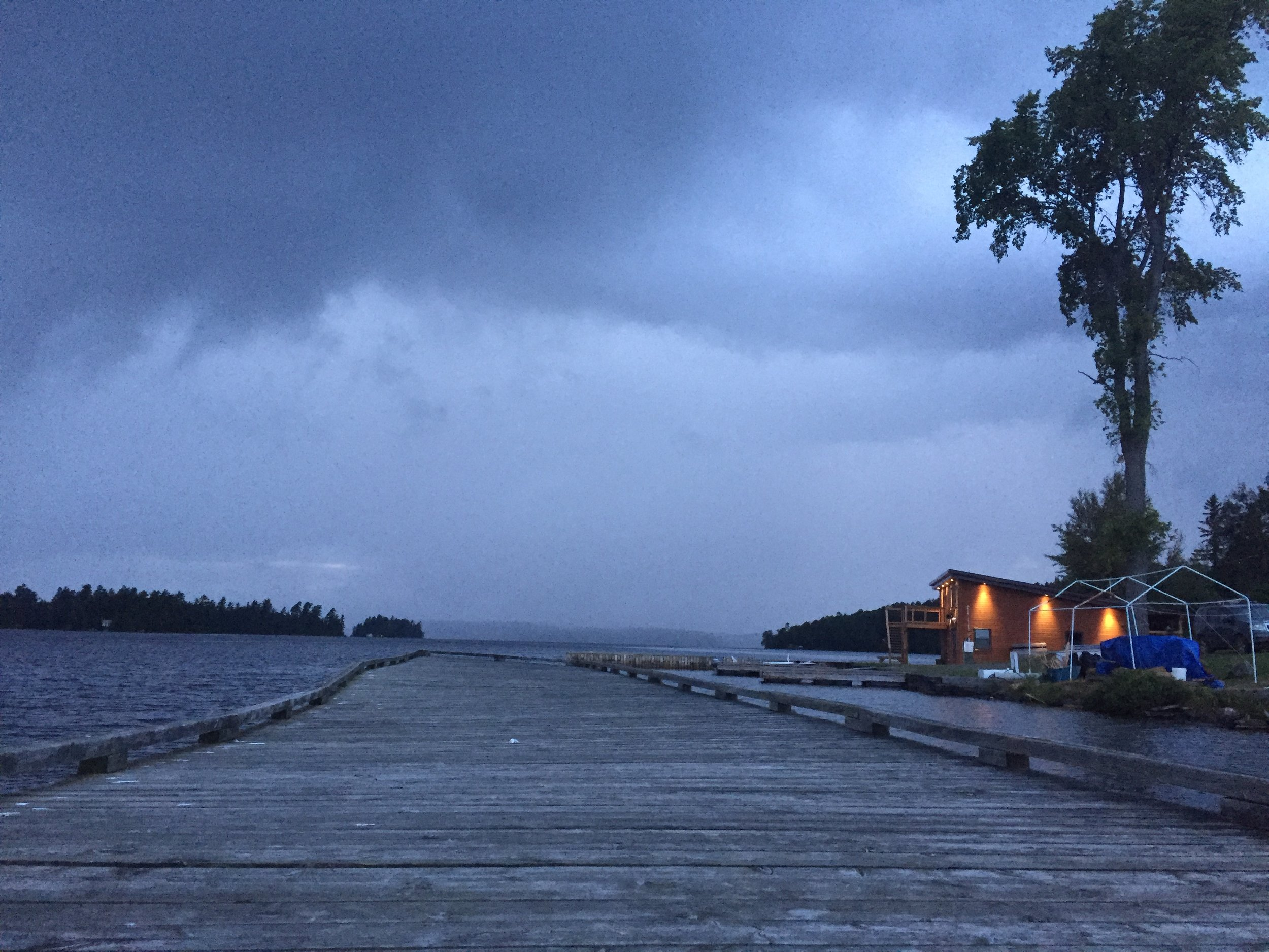 The canoe house lit up, as the storm comes in
