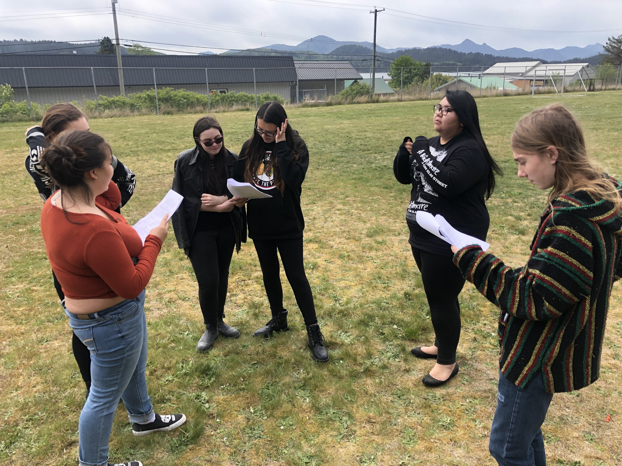 Outside in the school field, Team #HORRO go over the script