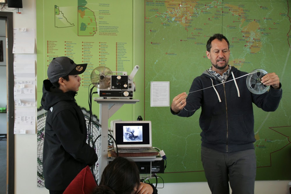 Paolo (right) shows Aaron how to load the film projector