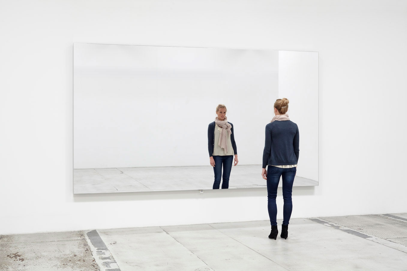 Mirror Wall - Jeppe Hein 2009 - jeppehein.net     A large mirror is mounted on the wall. As visitors enter the space, the surface of the mirror begins to flutter in a subtle wave-like motion. Visitors facing the mirror become irritated by the vibrating reflection of themselves and their surroundings. This sensation causes not only a vague feeling of dizziness but also a latent distrust of one's own eyes and spatial perception. As the mirror displays a different picture of the space, viewers question their own position within the room.
