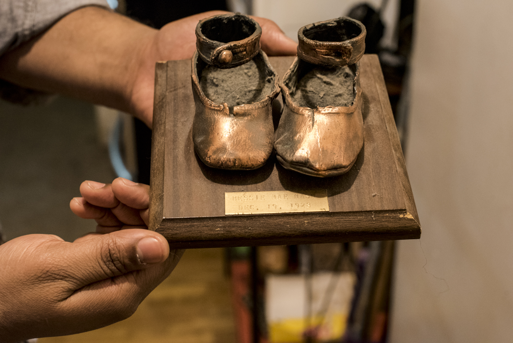 Kenneth Fontenelle holds the brass cast of his grandmother's (Bessie Fontenelle's) first shoes. (C) Harriet Dedman, 2016