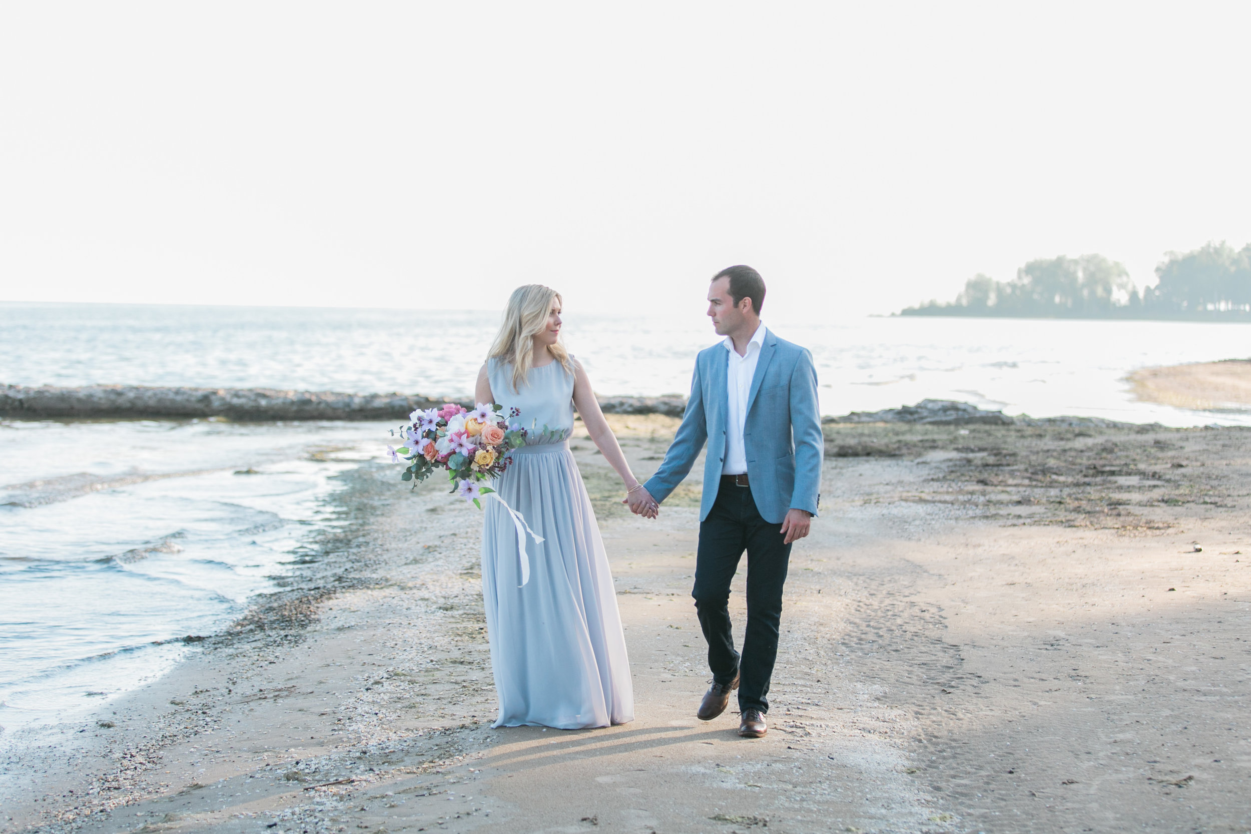 amanda cowley events niagara wedding planner beach engagement session holding hands