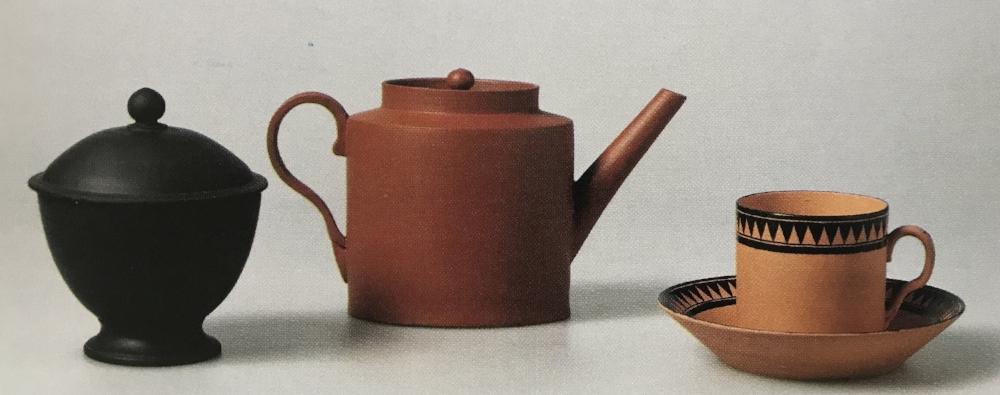 Group of Wedgwood Dry Body Teawares. From left: black basalt sugar bowl, 1874; red stoneware teapot 1931, stoneware tea bowl and saucer, 1947