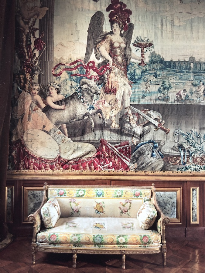 At Château du Champ de Bataille, above a Georges Jacob sofa bearing the stamps of Maire-Antoinette at the chateau of Fontainebleau, a Brussels tapestry depicts the signs of the zodiac and months of the year. Here, a war allegory represents the month of March while in the middle ground, gardeners tend a handsome French garden.
