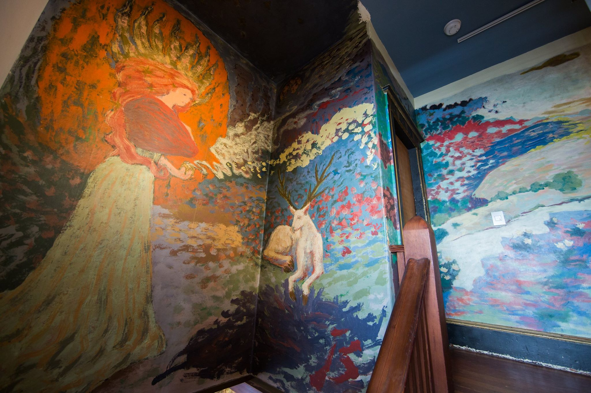 Hallway mural by Jess picturing a deity with her hair on fire, a stag and a mystical medieval romantic fantasy world that continues down the corridor.