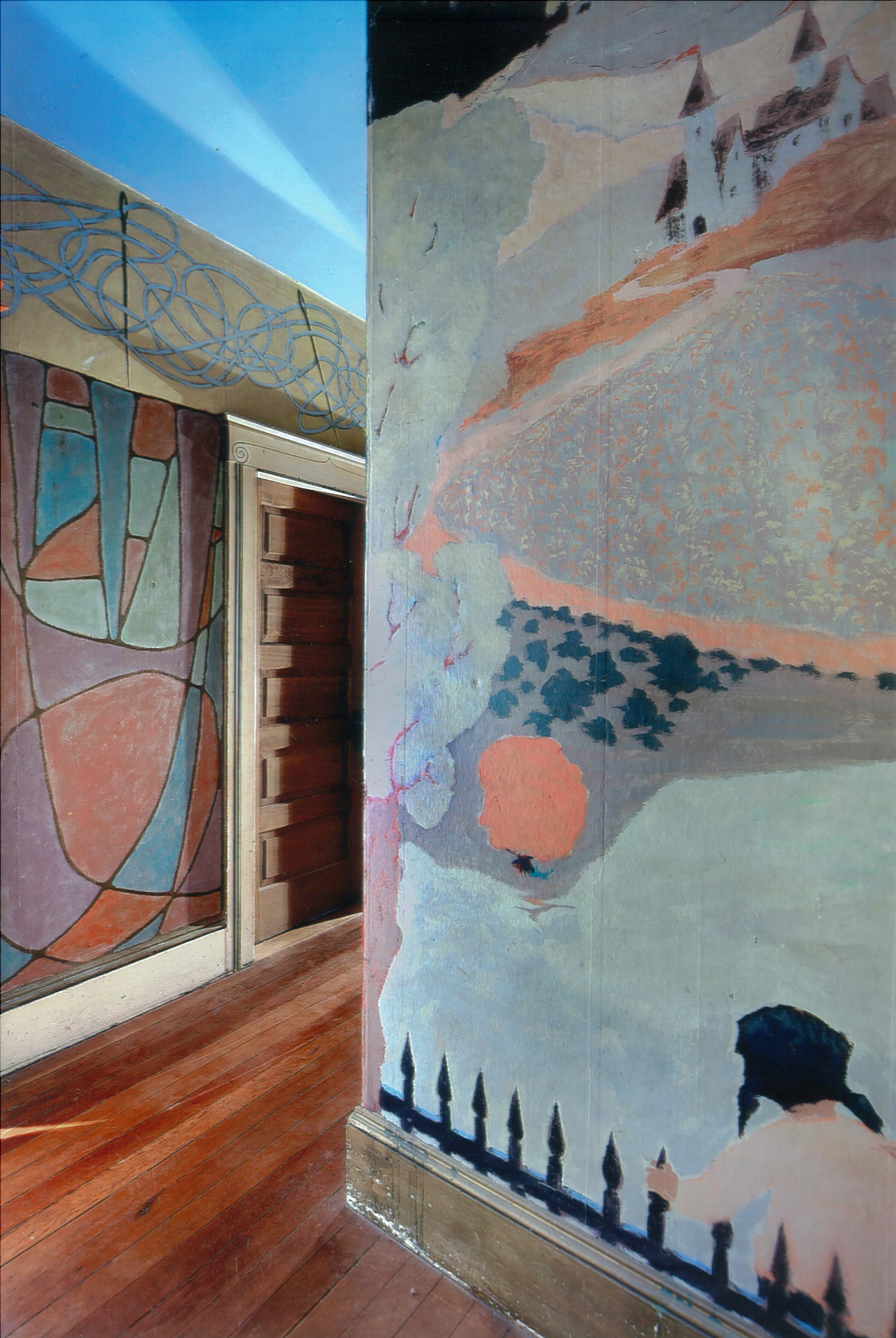 Jess hallway mural continued, picturing a girl looking over an iron fence at pale green fields and a distant castle atop a mountain.