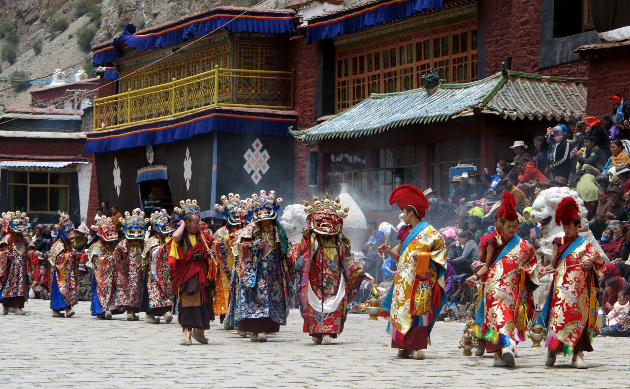 Monks in elaborate costumes and masks parade around the courtyard during the Tsurphu Monastery festival and cham dance performance.