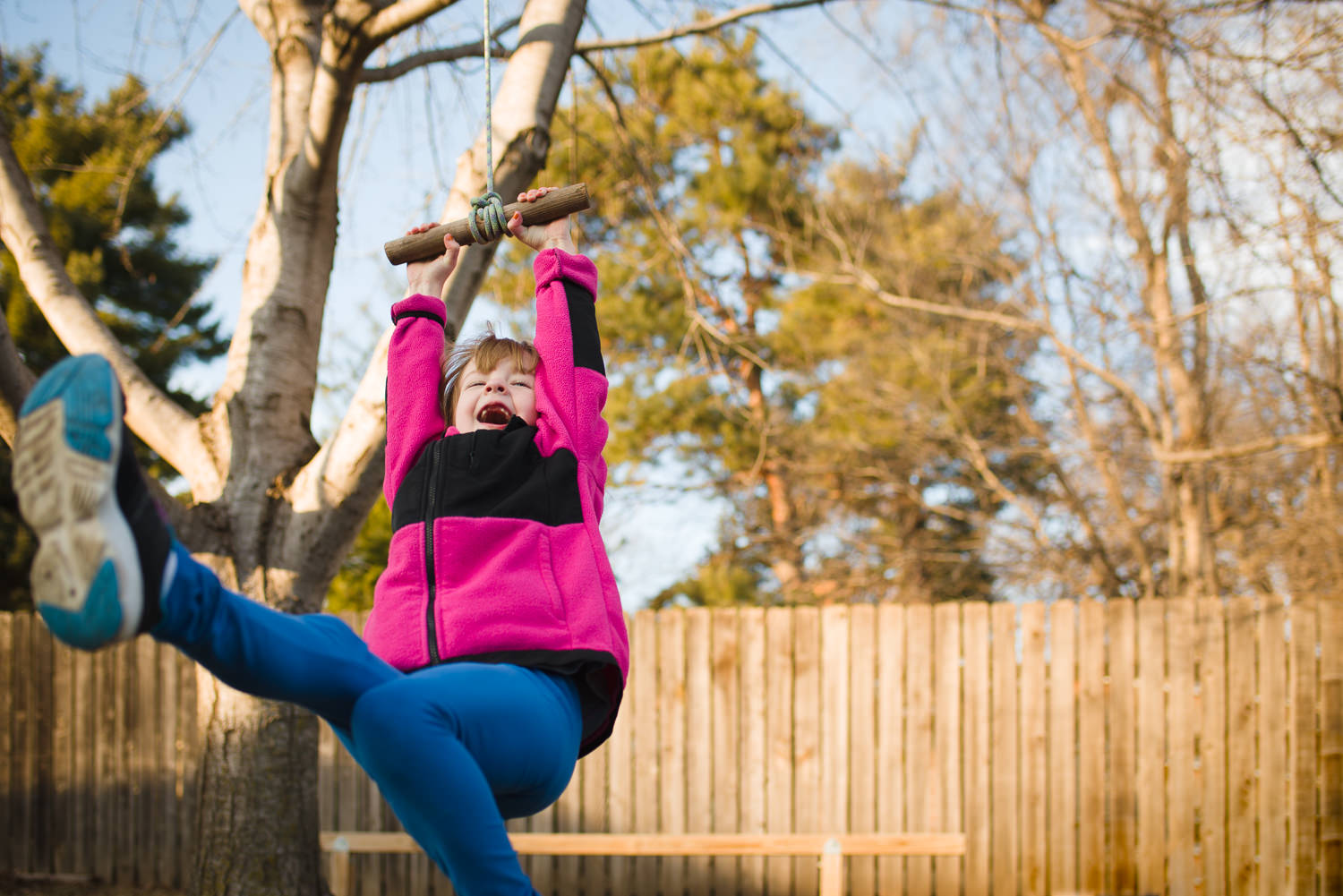 girl in pink jacket on a tree rope swing in my backyard, Lincoln, Nebraska