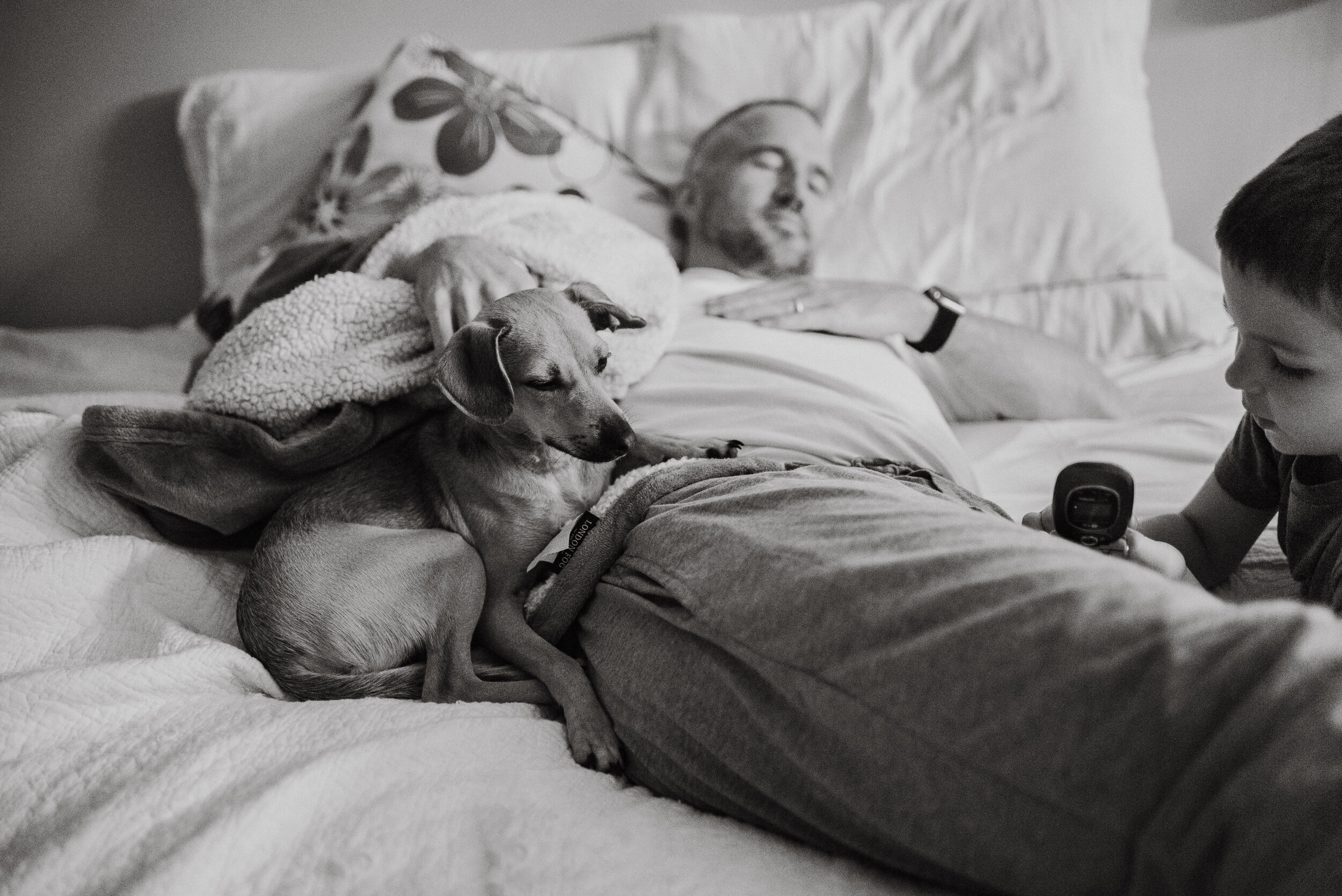 Man and dog asleep on a bed, black and white.
