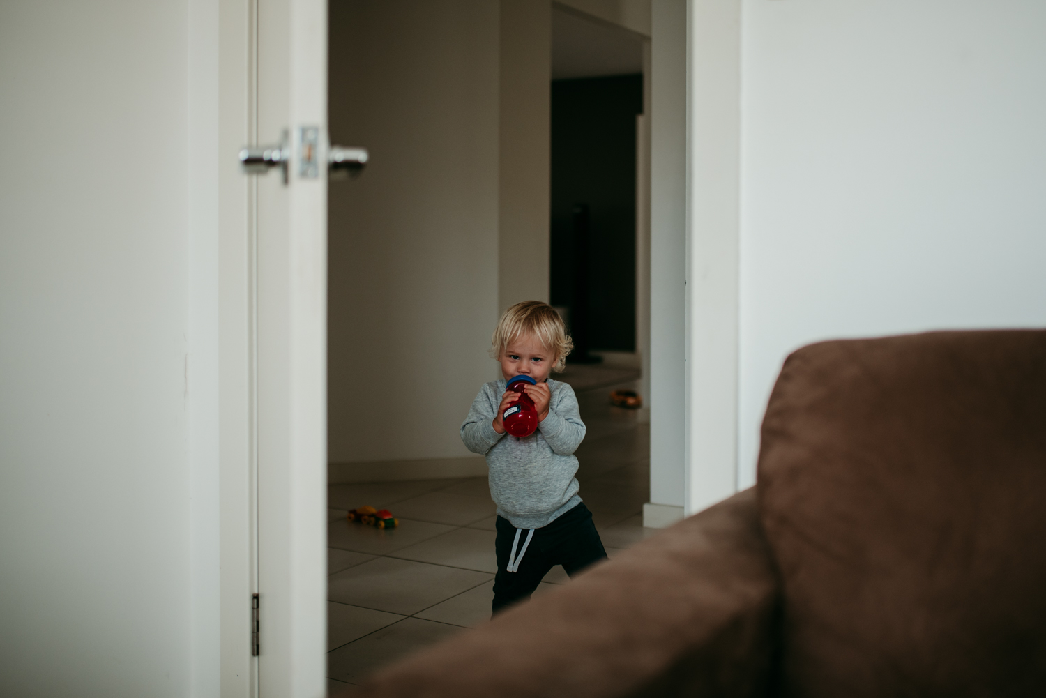 In this image, I love how the negative space either side of the doorframe leads the eye right to my cheeky monkey. I even love the scattered toys in the image... Because that's what life with kids is like!