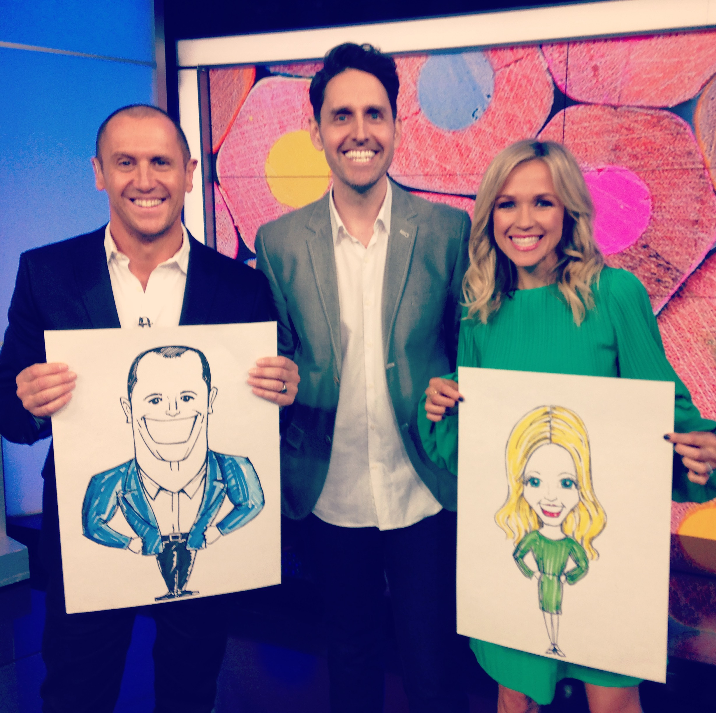 Larry Emdur and Sarah Cummings from The Morning Show on 7 holding up their caricatures drawn by author and illustrator Matt Cosgrove.