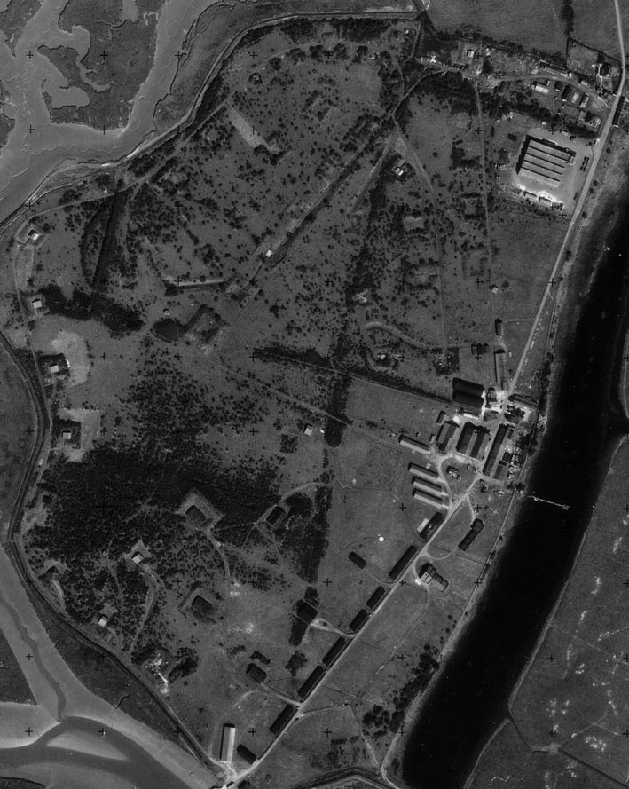 An RAF aerial photograph from 1953 clearly showing buildings and blast mounds all around the site.