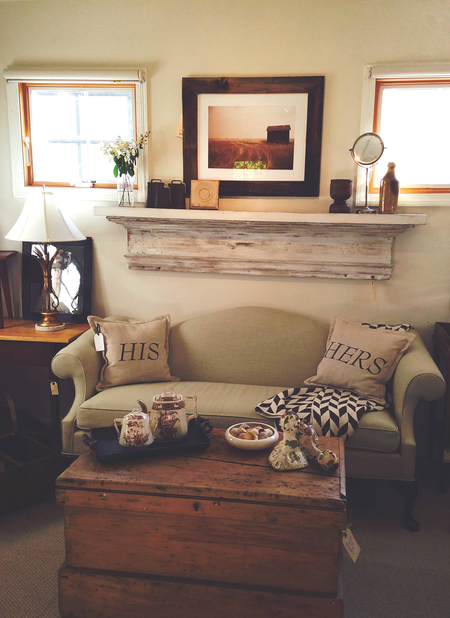 We brought this classic vintage Chippendale style love seat into the 21st century by recovering it in natural linen. It pairs prefectly with the warm patina of a well used antique pine tool trunk. Martin custom framed the contemporary sepia farm photograph in weathered barn wood.