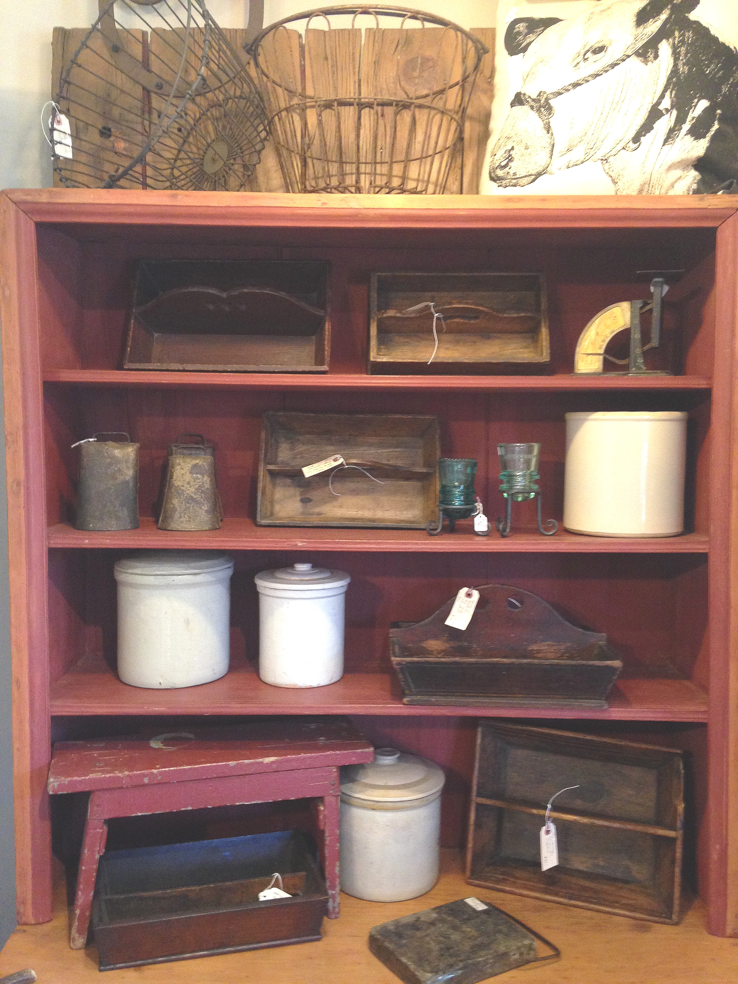 An assortment of antique knife/cutlery trays, stoneware crocks, cow bells, egg graders, and wire baskets round out this classic country display.