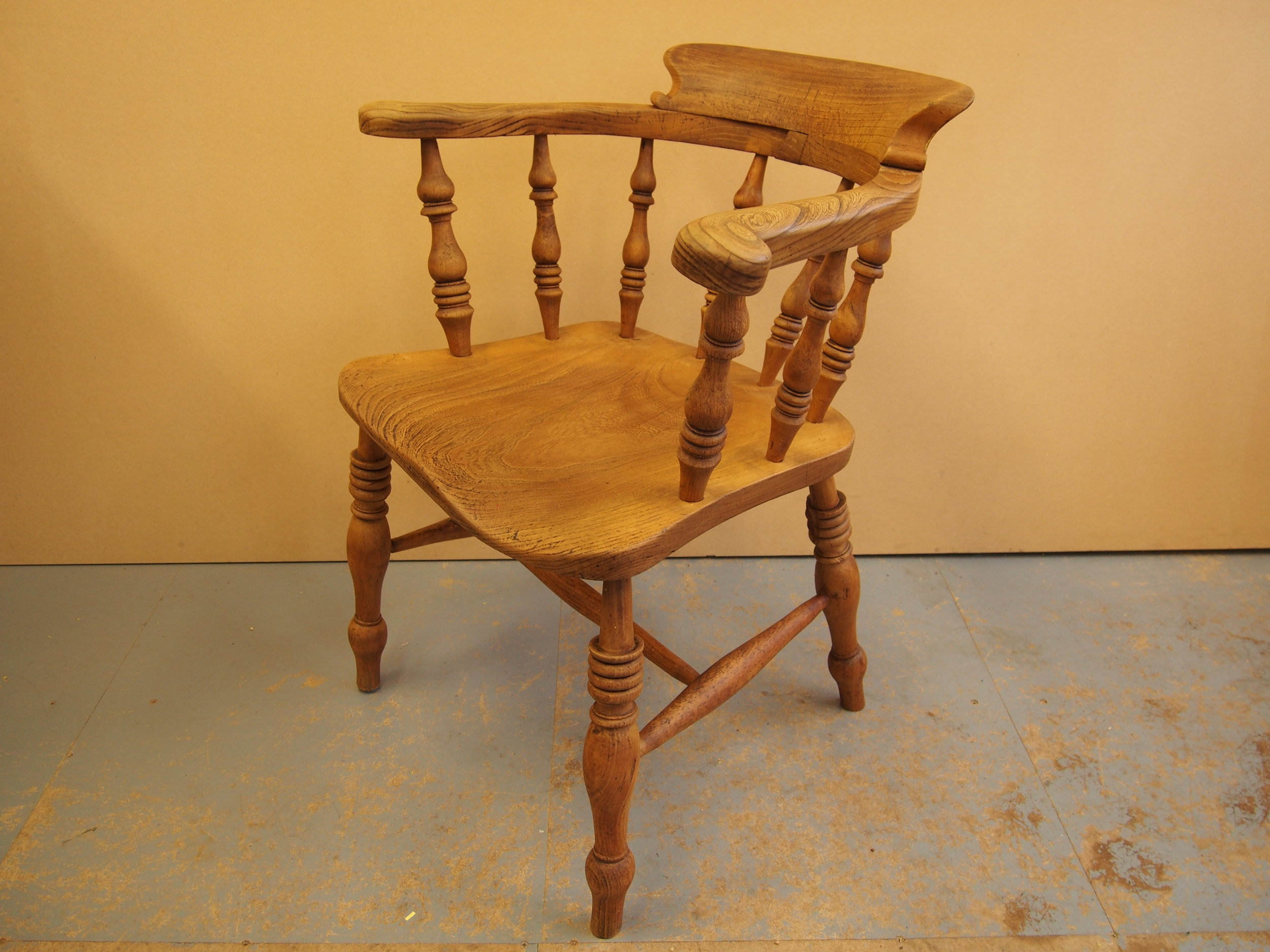 This sentimental Captain's Chair was commissioned to be restored and repaired to the given specification. The chair was to be stripped of its original finish and to have a light brown finish applied. One of the legs had fallen off that needed to be re-glued into position.  Several existing thick layers of the original finish were stripped back and it was evident that all of the legs and lower rails were loose, therefore each of these component's needed to be re-positioned and glued. The entire chair was lightly de-nibbed in order to make each surface smooth in preparation for the light brown varnish to be applied. A recommended final coat of wax was applied to further protect the surface from wear and discolouration.