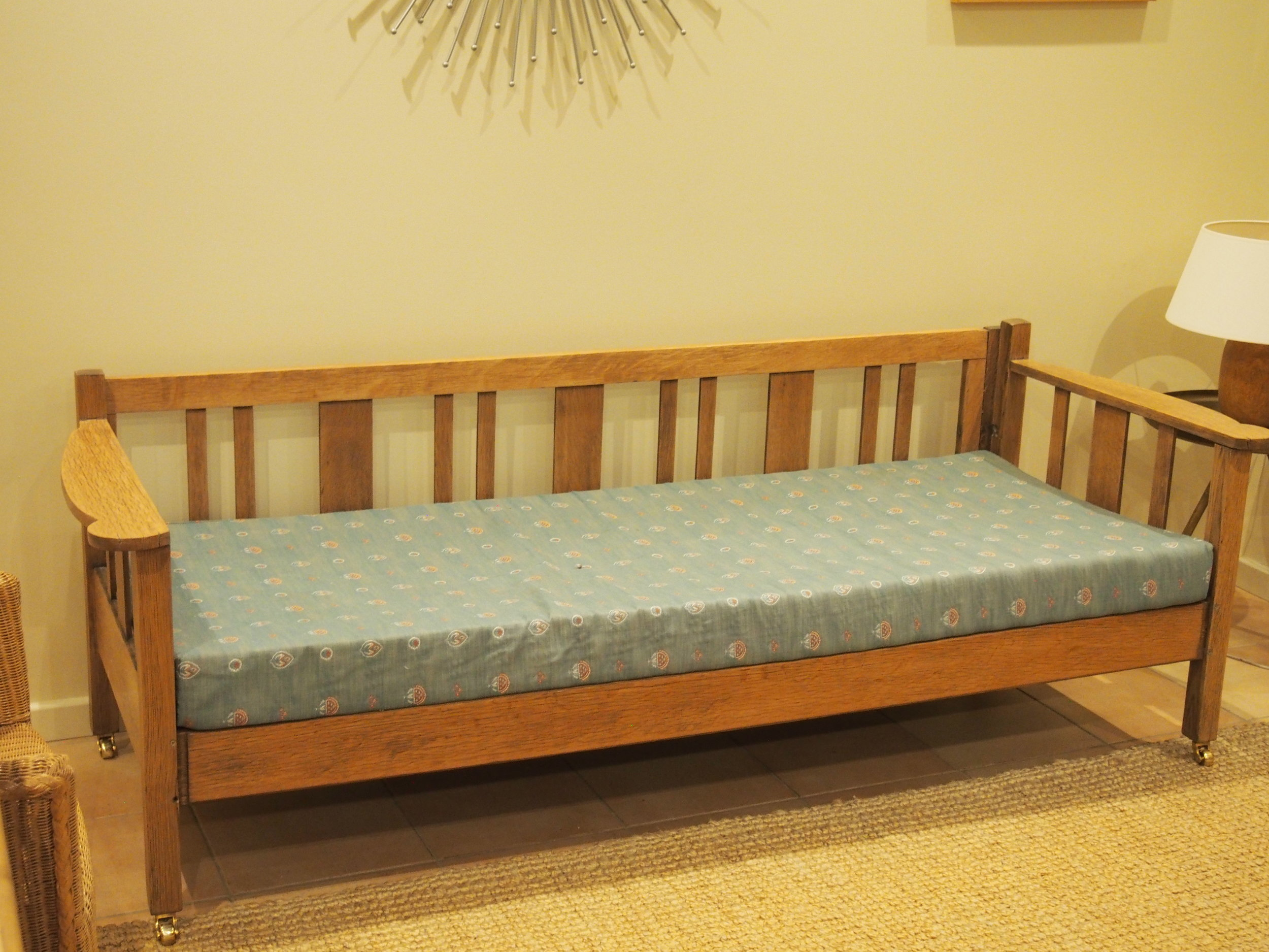 The 1920's Oak Day Bed was finished with a clear polish and protected with a wax finish. Four new solid brass castors were applied and a small split in the wood was glued close.
