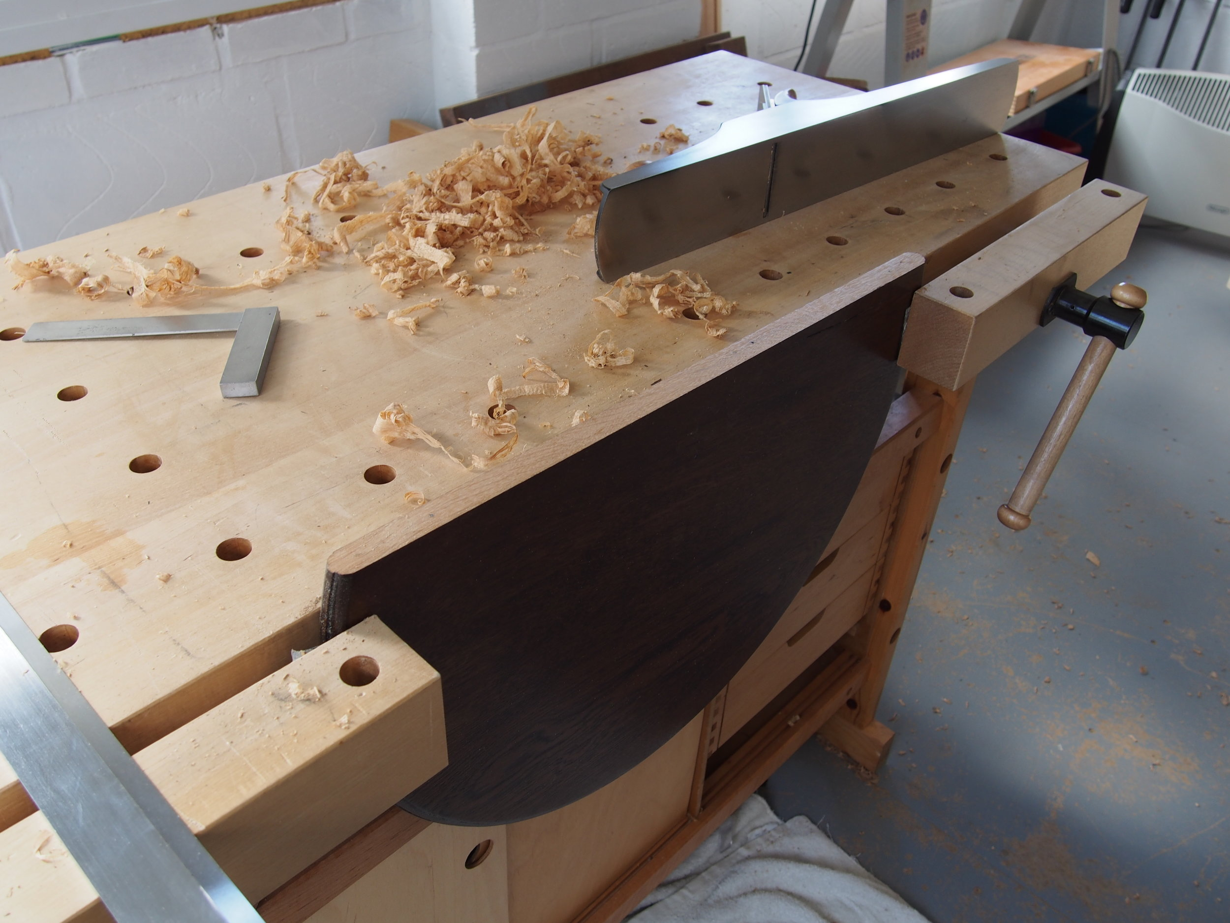 Hand planning smooth to remove a large split through the centre of a pub pedestal table, in preparation for glueing the top together with a clean tight joint.