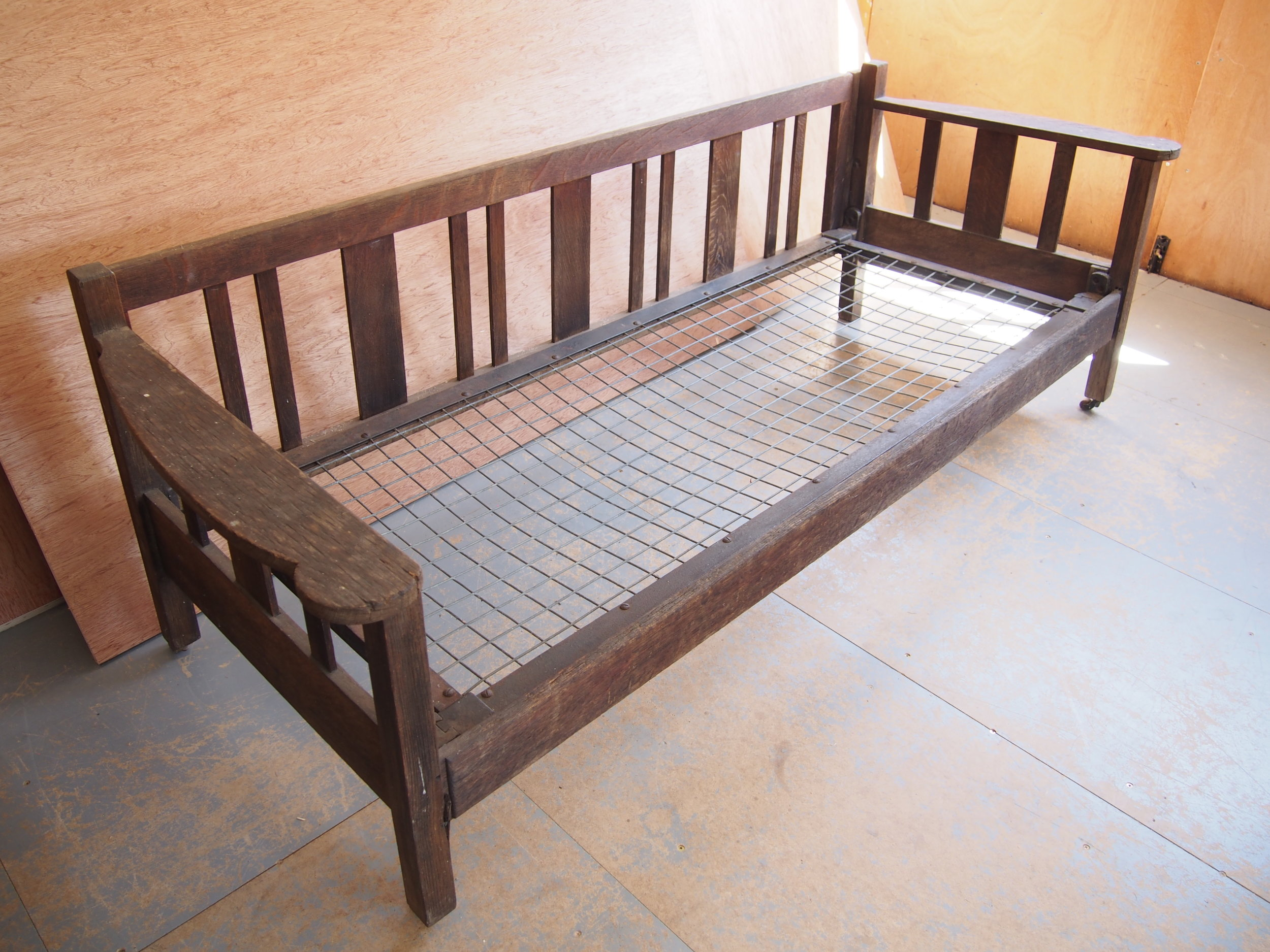Before Restoration of 1920's Heals Oak Day Bed   Presented with a thick dark surface finish, the pieces was to be stripped, to have a clear finish and to have new castors.