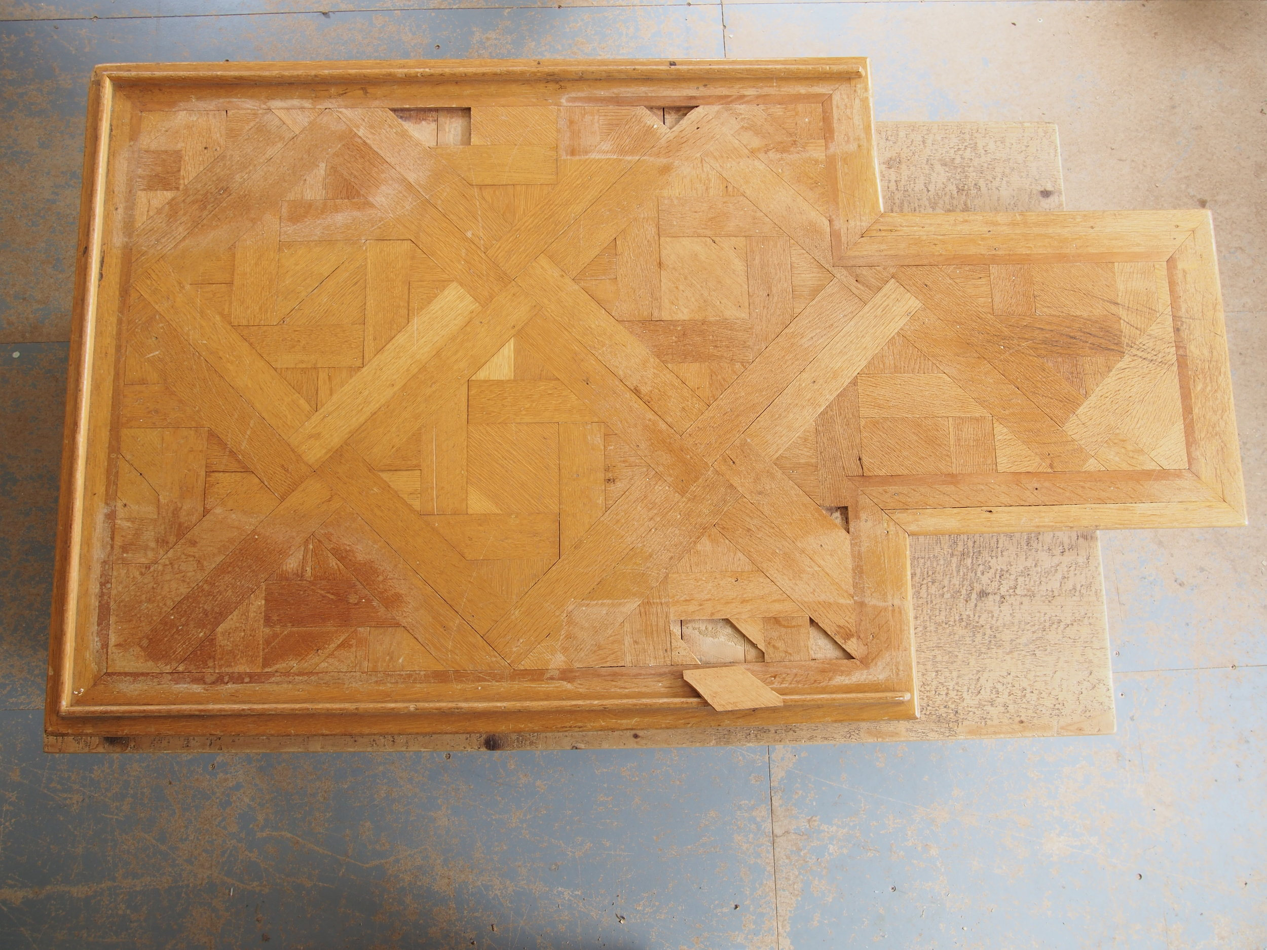 Before Restoration of Parquet patterned Oak Conference Table Plinth   The original condition had missing and broken sections and the surface finish was scratched and patchy.