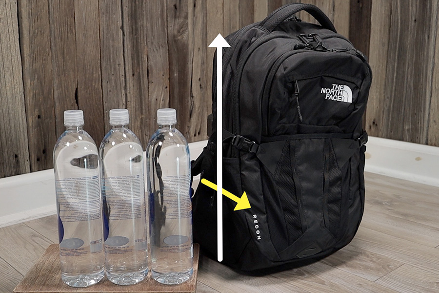 North Face Recon next to 1 liter water bottles. The extra carrying capacity can be found in the height and depth of the main compartment.