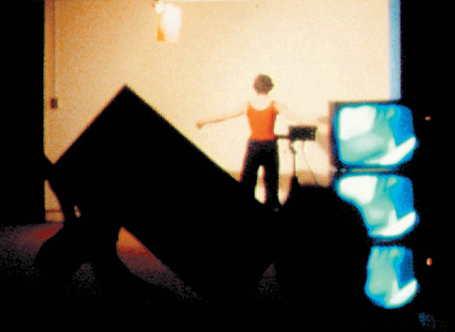 Still from Ellipsis, 1978, by Julie Harrison, a live performance at the Experimental Television Center, Binghamton, NY, including interaction between 4 dancers, 3 video cameras, and prerecorded videotapes sequenced/switched to 7 monitors.