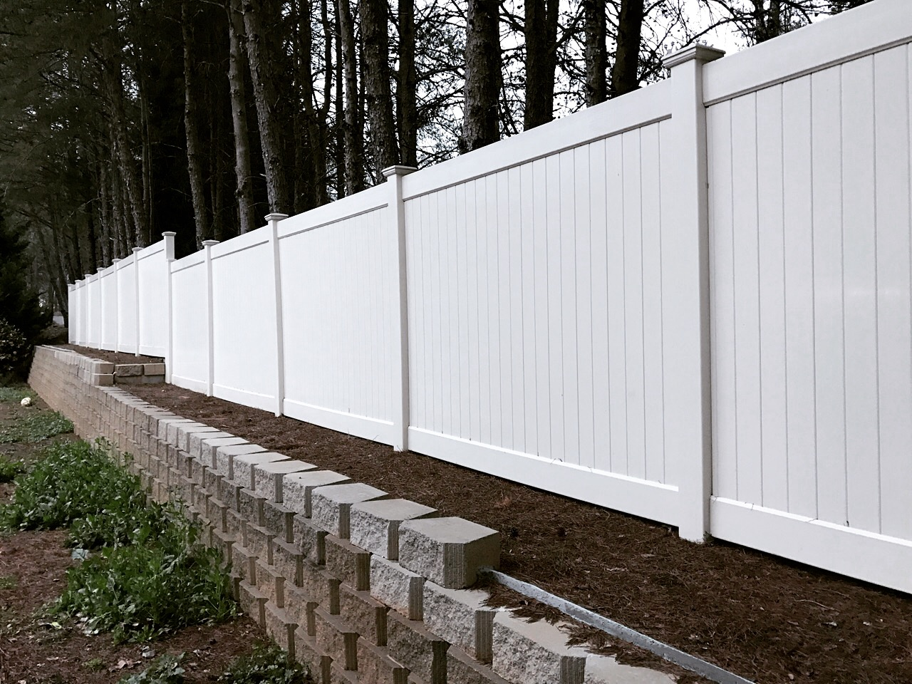 Solid privacy vinyl fence installed on top of a retaining wall