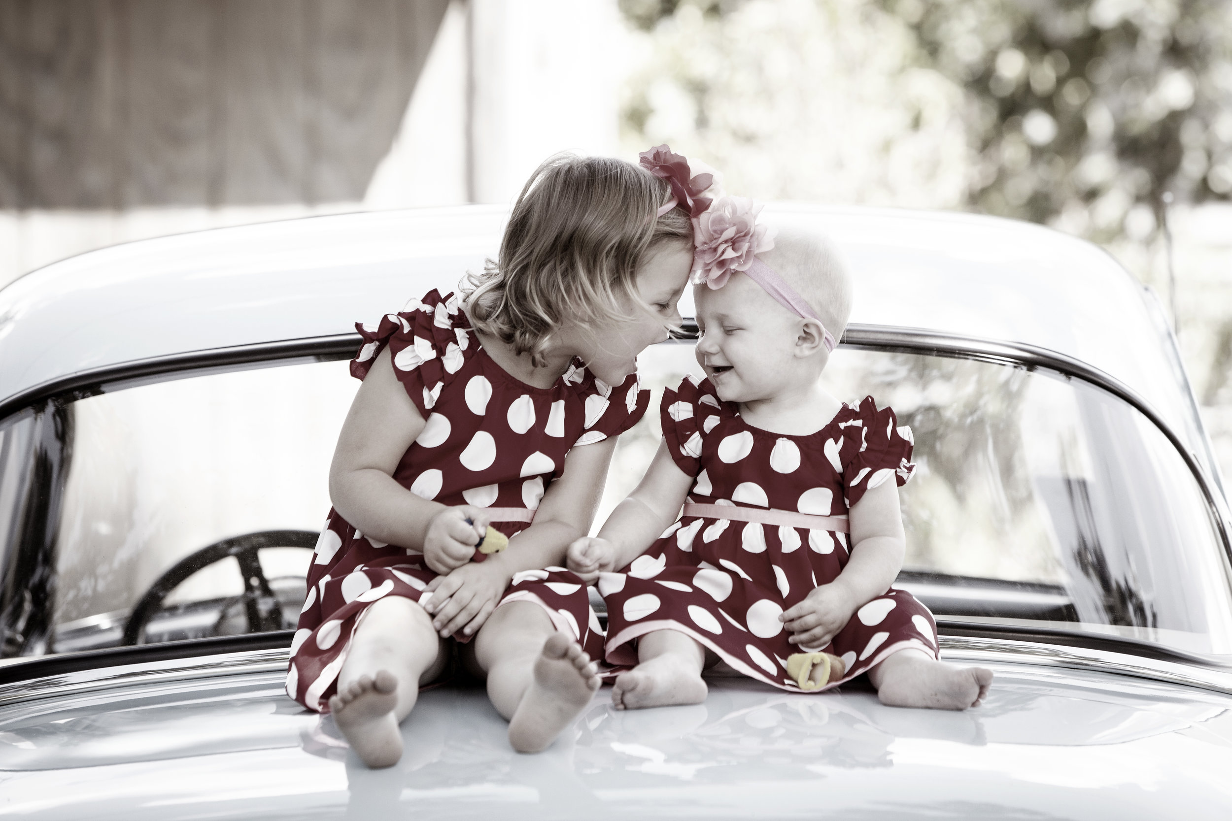 Two young sisters laughing on their family car