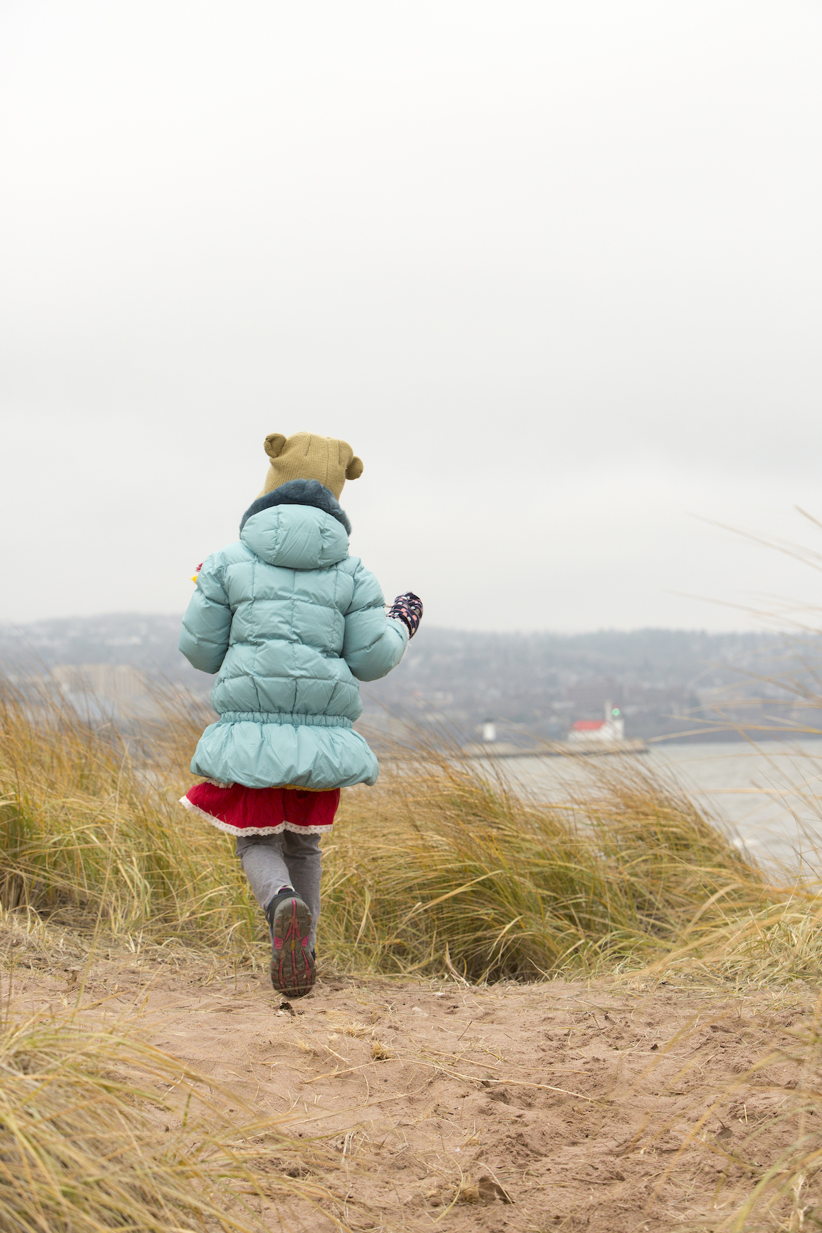 Cloudy day hike with young girl bundled up in a warm parka